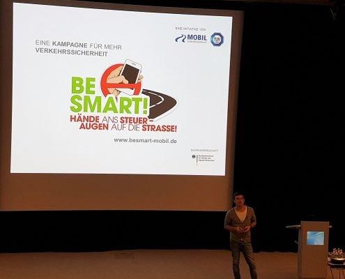 Ein junger Mann steht vor einer großen Leinwand mit BeSmart Präsentation