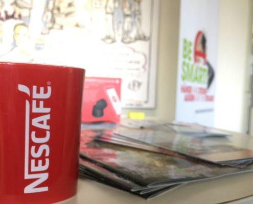 """Eine rote Tasse mit """"Nescafe""""-Aufschrift steht auf einem Tisch mit sehr viel BeSmart-Utensilien"""