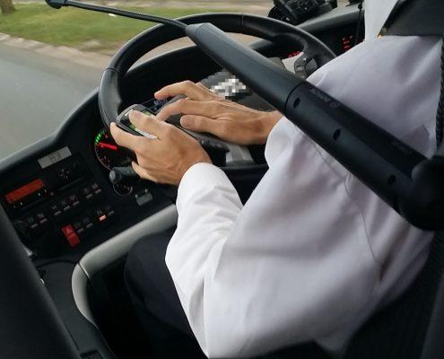 Busfahrer fährt in Bus mit Handy am Steuer