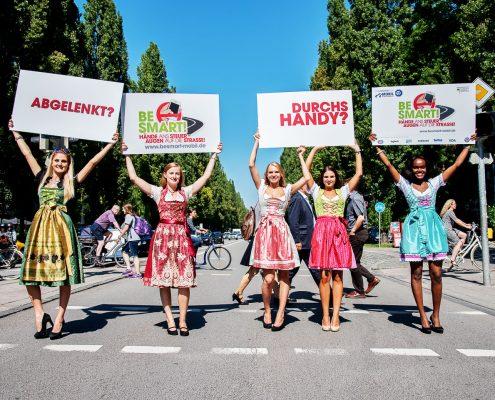 5 Mädchen in Dirndl halten bedruckte Schilder in die Luft