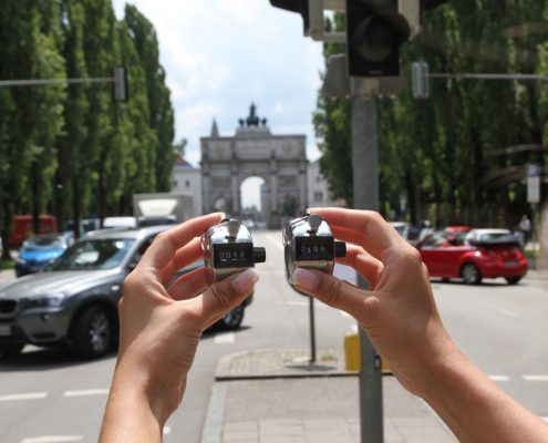 Zwei Hände halten jeweils einen Verkehrszähler, im Hintergrund eine belebte Straße