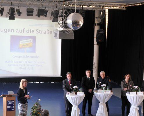 Fünf Erwachsene stehen an Stehtischen in einer Aula und eine Frau hält ein Mikrofon in der Hand