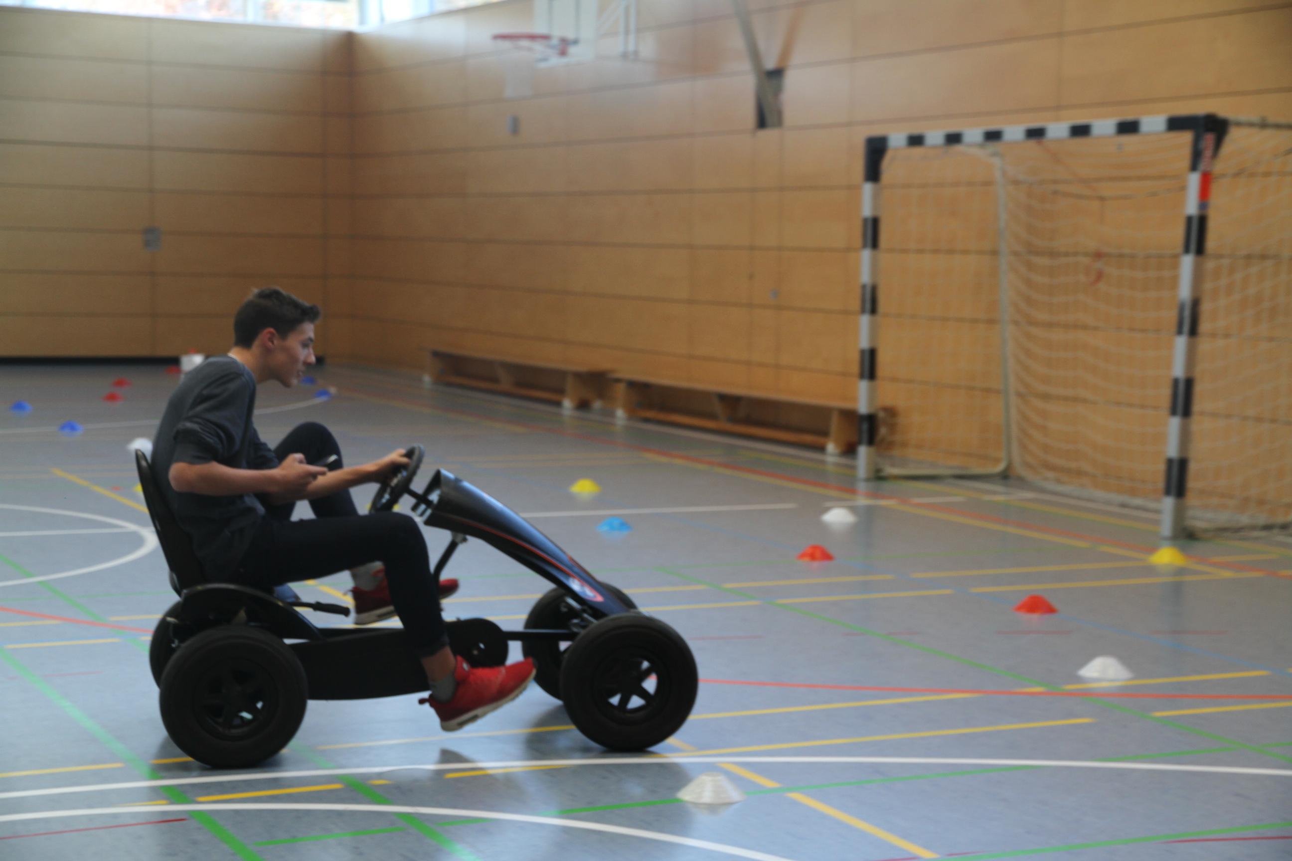 Ein Junge fährt mit einem Kettcar in einer Turnhalle um bunte Hütchen
