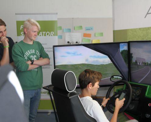 Ein Junge fährt mit dem Fahrsimulator und weitere sehen zu