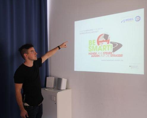 Junger Mann zeigt auf Projektion an Wand