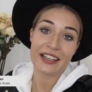 Eine junge Frau mit Hut guckt in die Kamera