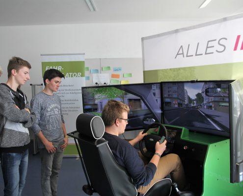 Ein Junge der mit dem Fahrsimulator fährt und drei weitere Jungs die zusehen und links von ihm stehen