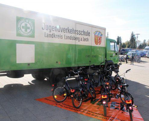 Ein grüner, großer Laster der Jugendverkehrsschule Landkreis Landsberg a. Lech auf einem Parkplatz und einigen Fahrrädern die vor diesem stehen