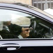 Mann mit Handy am Steuer eines schwarzen Wagens