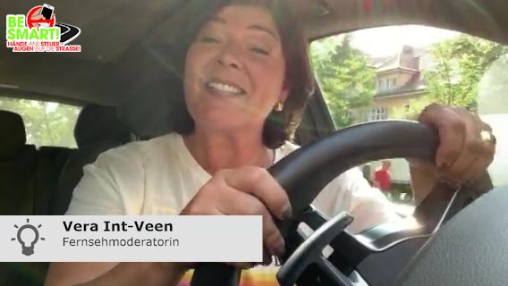 Vera Int-Veen sitzt im Auto und warnt vor Handy am Steuer