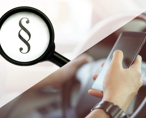 Handy am Steuer und Paragraphenzeichen unter Lupe