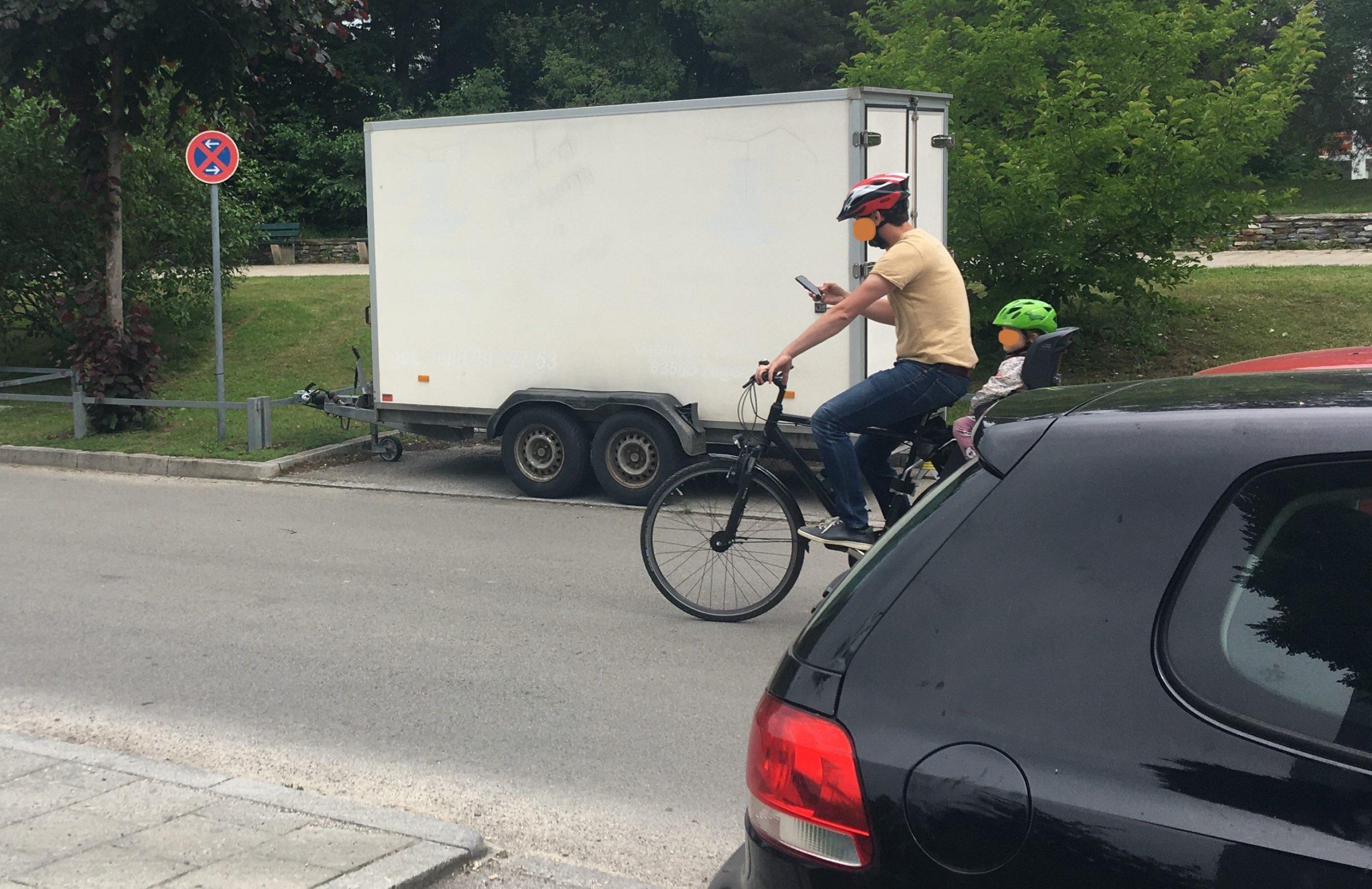 Fahrradfahrer mit Kind im Kindersitz und Handy in der Hand